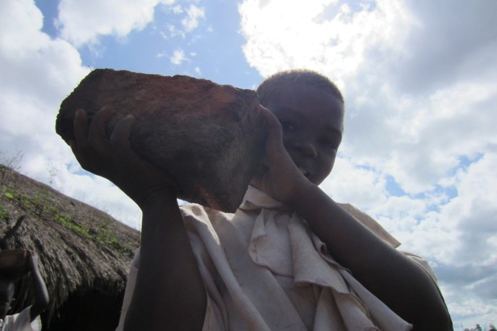 Future student in the Congo holding a brick